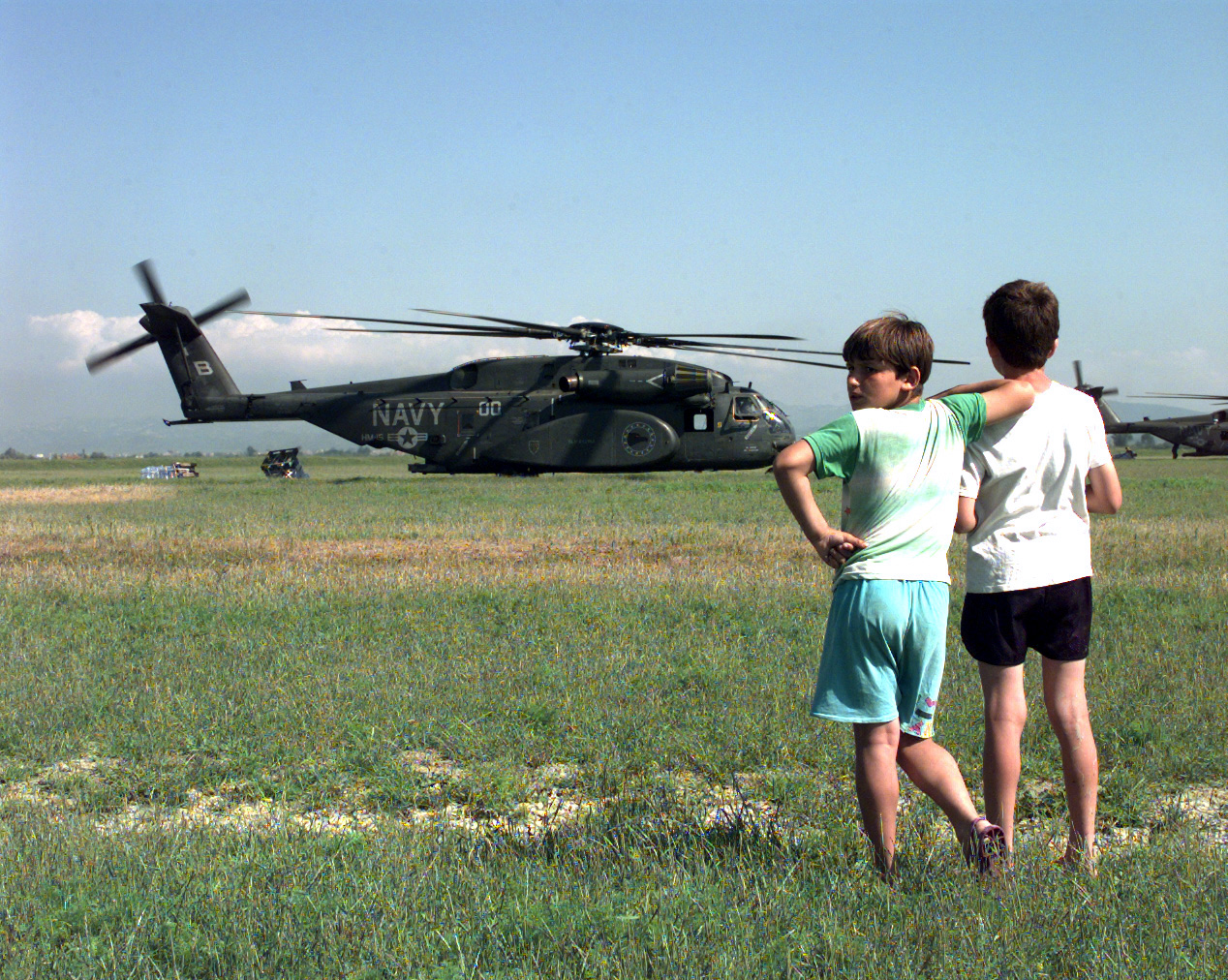 990513-F-5920L-001 	Two refugee children watch as relief supplies are unloaded from U.S. Navy MH-53E Sea Dragon helicopters at Camp Hope near Fier, Albania, on May 13, 1999, during Operation Sustain Hope.  Sustain Hope is the U.S. effort to bring in food, water, medicine, relief supplies, and to establish camps for the refugees fleeing from the Former Republic of Yugoslavia.  The Department of Defense has constructed Camp Hope to house up to 20,000 refugees.  The Sea Dragons are airlifting in supplies from the USS Inchon (MCS 12) which is operating in the Adriatic Sea.  DoD photo by Senior Airman Michelle Leonard, U.S. Air Force.  (Released)